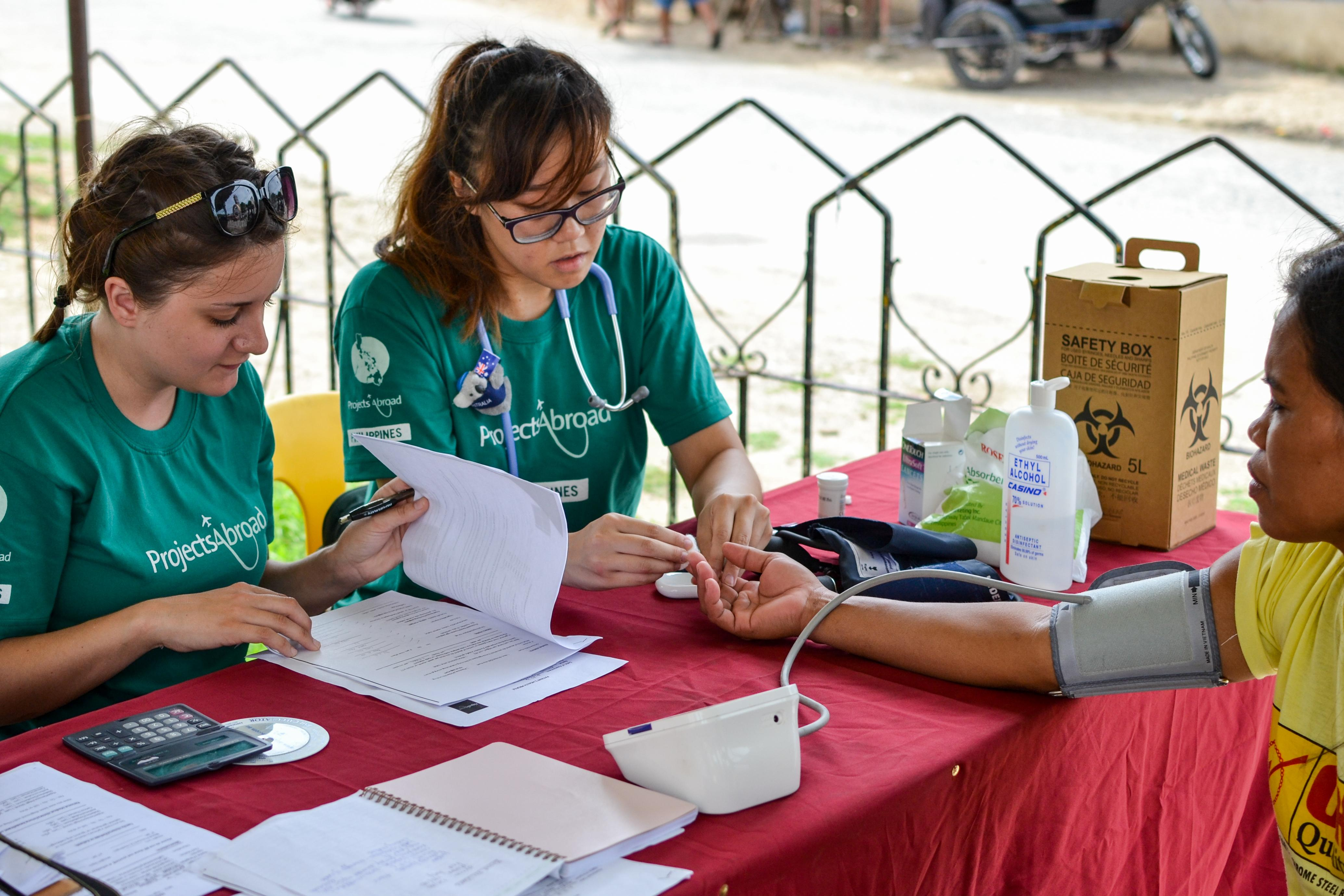 As part of the Projects Abroad Public Health group work in the Philippines, interns check the blood pressure of patents.